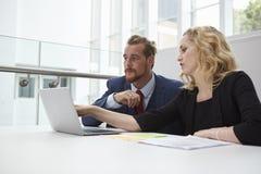 2 предпринимателя используя компьтер-книжку на столе в современном офисе Стоковые Изображения