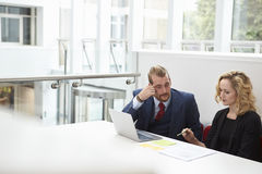 2 предпринимателя используя компьтер-книжку на столе в современном офисе Стоковая Фотография RF