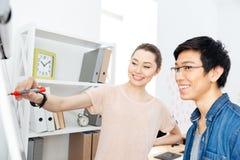 2 предпринимателя писать на flipchart в офисе Стоковая Фотография RF