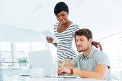 2 предпринимателя работая в офисе и обсуждая новые идеи Стоковые Фотографии RF