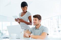 2 предпринимателя работая в офисе и обсуждая новые идеи Стоковое Изображение