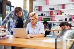 2 предпринимателя работая на компьтер-книжке в занятом офисе Стоковое Фото