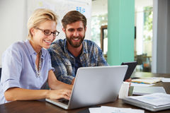 2 предпринимателя работая на компьтер-книжке в офисе совместно Стоковые Фотографии RF
