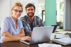 2 предпринимателя работая на компьтер-книжке в офисе совместно Стоковое фото RF