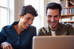 2 предпринимателя работая на компьтер-книжке в офисе Стоковые Фотографии RF