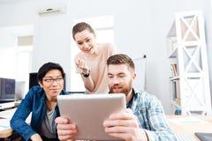 3 предпринимателя работая с таблеткой совместно Стоковая Фотография