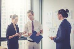 3 предпринимателя стоя в современном офисе говоря в конференц-зале Стоковое Изображение RF