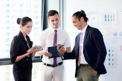 3 предпринимателя стоя в современном офисе смотря телефон и говоря встречу Стоковая Фотография
