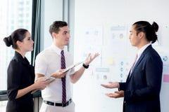3 предпринимателя стоя в современном офисе смотря файл documeeting Стоковые Фотографии RF