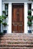 Представительная деревянная дверь с фигурной стрижкой кустов на каждой стороне и лестницы кирпича в Чарлстоне, Южной Каролине стоковое фото