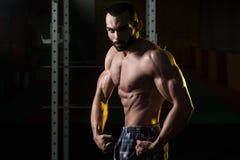 Представление комода мышц молодого культуриста изгибая бортовое Стоковые Фото