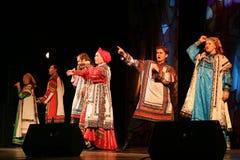 Представление на этапе актеров, певец-соло, певиц и танцоров песни русского национального театра Стоковые Изображения