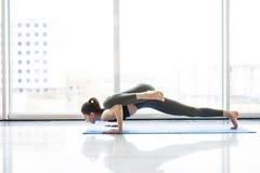 Представление планки Йога молодой sporty женщины практикуя протягивая exercisewearing sportswear около окна пола с видом на город Стоковая Фотография