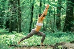 Представление ратника йоги женщиной на зеленой траве в парке вокруг штыря Стоковые Фото
