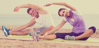 Представления йоги Гая и девушки практикуя сидя на пляже морским путем на da Стоковое Изображение