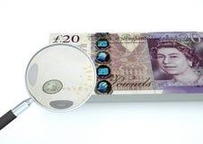 представленные 3D деньги Великобритании при увеличитель расследуют валюту изолированный на белой предпосылке Стоковое Изображение
