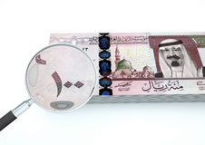 представленные 3D новые деньги Саудовской Аравии при увеличитель расследуют валюту изолированный на белой предпосылке стоковое изображение