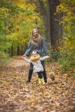 Представлять в парке осени, желтые жизни матери и маленькой блондинкы дочери усмехаясь вокруг Стоковые Фотографии RF