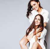 Представлять девушки 2 близнецов сестер, делая selfie фото, одел такую же белую рубашку, разнообразные друзей стиля причёсок, обр Стоковое Фото