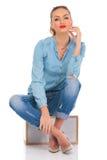 Представлять девушки усаженный в студию на коробке при пересеченные ноги Стоковое Фото