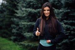 Представлять красивой женщины спортсмена брюнет фитнеса отдыхая после разрабатывает работать на парке Стоковые Фотографии RF