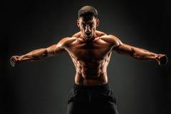 представлять культуриста Человек muscled фитнесом на темной предпосылке Реветь для мотивировки стоковое фото