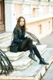 Представлять молодой жизнерадостной девушки усмехаясь на шагах улицы города Стоковые Фото