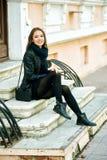 Представлять молодой жизнерадостной девушки усмехаясь на шагах улицы города Стоковая Фотография RF