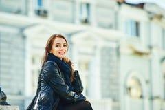 Представлять молодой жизнерадостной девушки усмехаясь на шагах улицы города Стоковые Изображения