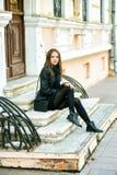 Представлять молодой жизнерадостной девушки усмехаясь на шагах улицы города Стоковая Фотография