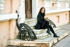 Представлять молодой жизнерадостной девушки усмехаясь на шагах улицы города Стоковое Фото