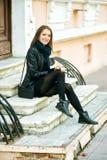 Представлять молодой жизнерадостной девушки усмехаясь на шагах улицы города Стоковое Изображение