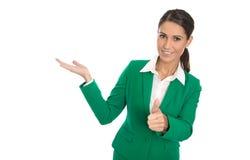 Представляющ изолированную коммерсантку в зеленом платье с большим пальцем руки вверх Стоковая Фотография