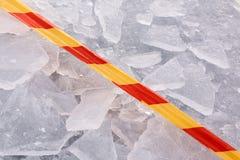 Предупреждающая лента и сломленные части льда Стоковые Изображения