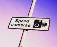 Предупредительный знак камеры скорости против фиолетовой розовой предпосылки Стоковые Фото