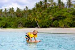 Прибой детей на тропическом пляже Каникулы с ребенком стоковая фотография rf