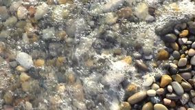 Прибой моря на пестротканых отполированных камнях и камешках акции видеоматериалы