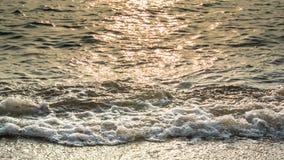 Прибой моря с светом захода солнца Стоковые Фото