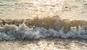 Прибой моря с светом захода солнца Стоковые Изображения