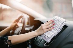 Приборная панель автомобиля чистки женщины стоковое фото rf