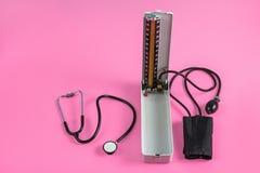 Приборы и стетоскоп датчика кровяного давления на розовой предпосылке Стоковое Изображение