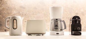 Приборы кухни электрические на белой поверхности Красочная, запачканная предпосылка Закройте вверх по взгляду, деталям стоковое изображение rf