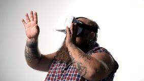 Прибор виртуальной реальности тучного бородатого парня наблюдая видеоматериал