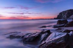 Прибрежный заход солнца на скалистом пляже в Корнуолле, Англии Стоковая Фотография