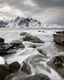 Прибрежный ландшафт в зиме с движением воды между большими камнями стоковая фотография rf