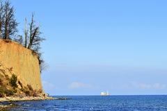 Прибрежный пейзаж с силуэтом корабля на горизонте Стоковое Фото