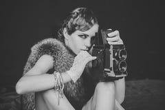 Приведенная в действие девушка Девушки стороны вопросов Женщина с ретро волосами, составом и старой камерой стоковое фото