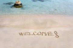 Приветственное сообщение написанное на белом песке, с тропическим морем развевает в предпосылке стоковое фото
