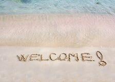 Приветственное сообщение написанное на белом песке, с тропическим морем развевает в предпосылке стоковые фотографии rf