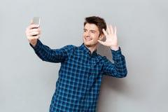Приветствие молодого человека с кто-нибудь пока делающ видео- звонок или selfie стоковые фото